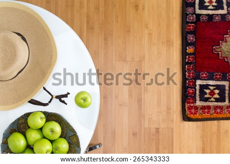 High Angle View of Healthy Fresh Green Apples and Brown Hat on Top of a White Table on the Wooden Floor with Carpet. - stock photo