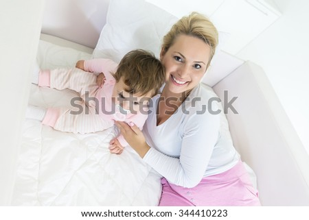 High angle view of hugging mother and baby in the bed.Mother looking at camera.Shallow doff - stock photo