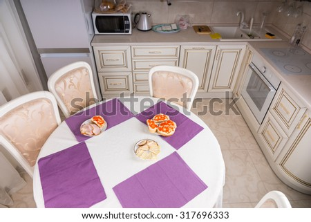 High Angle View of Kitchen with Dining Table Set for Four with Purple Placemats and Plates of Appetizers Prepared for Company - stock photo