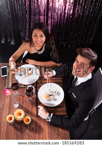 High angle view of loving young couple having meal at restaurant table - stock photo