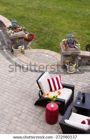 High Angle View of Luxury Patio with Outdoor Living Room Furniture and Stone Pillars Decorated with Colorful Flowers - Red Wine Served near Comfortable Chairs with Striped Cushions on Stone Patio - stock photo