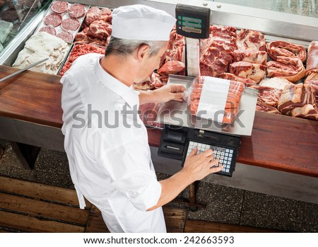 High angle view of male butcher weighing sausages at display cabinet in butchery - stock photo
