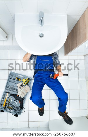 High Angle View Of Male Plumber Repairing A Sink In Bathroom - stock photo