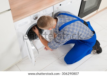 High Angle View Of Male Worker In Overall Making Washer - stock photo