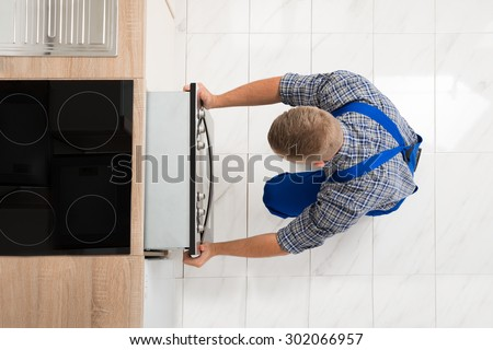 High Angle View Of Man In Overall Repairing Oven In Kitchen - stock photo
