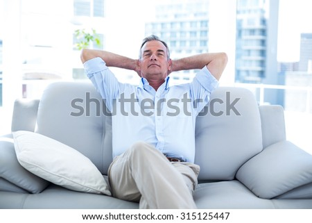 High angle view of man relaxing on sofa st home - stock photo