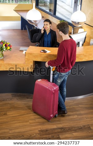 High angle view of man with luggage standing at hotel reception desk - stock photo
