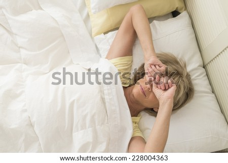 High angle view of mature woman rubbing eyes while lying in bed at home - stock photo