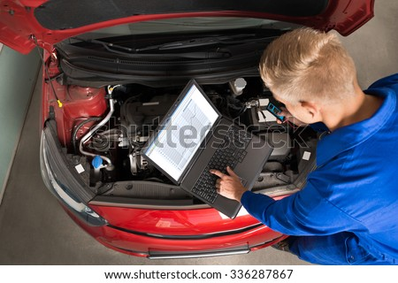 High Angle View Of Mechanic Using Laptop To Repair Car In Garage - stock photo