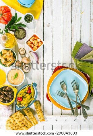 High Angle View of Mediterranean Appetizers and Colorful Plates Arranged on Rustic White Wooden Picnic Table with Copy Space - stock photo