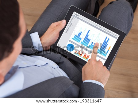 High angle view of mid adult businessman comparing graphs on digital tablet in office - stock photo