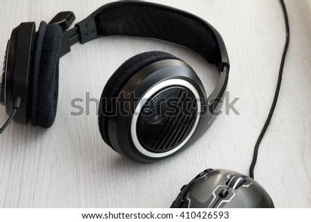 High Angle View of Modern  Audio Headphones with Cord and Mouse on Grey Desk Background with Copy Space - stock photo