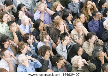 High angle view of multi ethnic people covering their eyes - stock photo