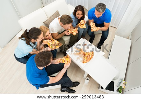 High Angle View Of Multiethnic Friends Eating Pizza - stock photo