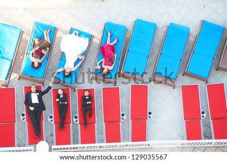 High angle view of newly wedded couple with bridesmaids and groomsmen lying on lounge chairs. horizontal shot. - stock photo