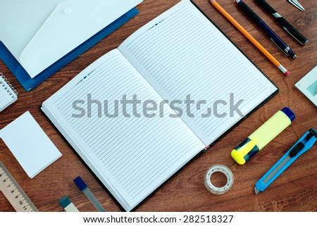 High Angle View of Office or School Supplies Arranged Neatly Around Notebook Open to Blank Page on Wooden Desk Surface - stock photo