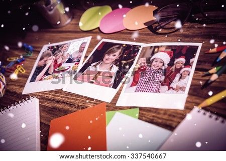 High angle view of office supplies and blank instant photos against extended family saying grace before christmas dinner - stock photo