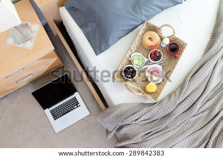 High Angle View of Open Laptop on Floor Beside Unmade Bed in Hotel Room with Wicker Breakfast Tray - stock photo