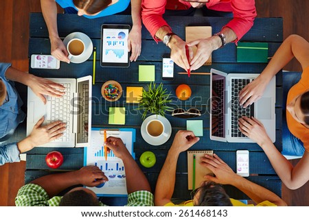 High angle view of people working together at one table - stock photo
