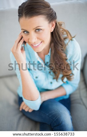 High angle view of pretty woman calling on phone sitting on cosy sofa - stock photo