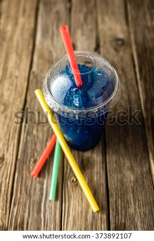 High Angle View of Refreshing and Cool Frozen Blue Fruit Slush Drink in Plastic Cup with Lid Served on Rustic Wooden Table with Collection of Colorful Straws - stock photo