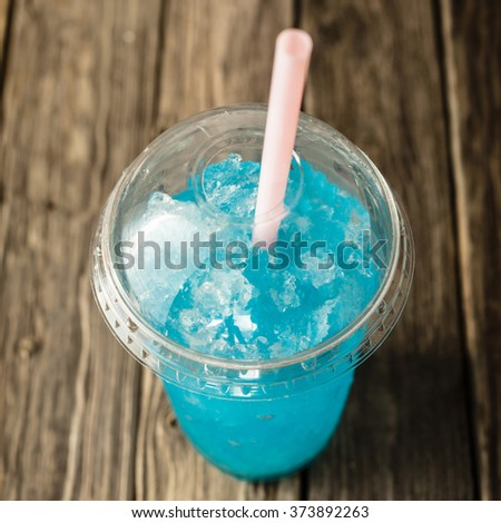 High Angle View of Refreshing and Cool Frozen Turquoise Fruit Slush Drink in Plastic Cup with Lid Served on Rustic Wooden Table with Pink Drinking Straw - stock photo