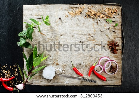 High Angle View of Rustic Cutting Board with Various Fresh Herbs, Spices, and Peppers Scattered on its Surface with Copy Space - stock photo
