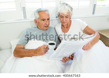 High angle view of senior couple reading newspaper on bed at home - stock photo