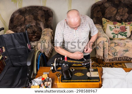 High Angle View of Senior Man Working at Old Fashioned Sewing Machine in Living Room at Home with Wheelchair Nearby - stock photo