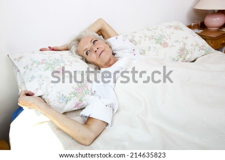 High angle view of senior woman looking away while lying in bed at home - stock photo
