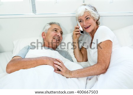 High angle view of senior woman with man talking on phone at bed - stock photo