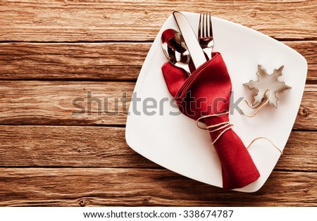 High Angle View of Silver Cutlery Set Wrapped in Red Linen Napkin and Snowflake Shaped Cookie Cutter on Stylish Square White Plate with Rustic Wooden Background with Copy Space - stock photo