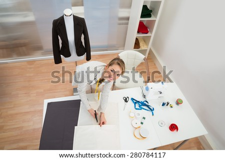 High Angle View Of Smiling Fashion Designer Cutting Fabric In Studio - stock photo
