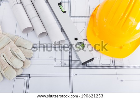 High angle view of spirit level; hardhat and gloves on blueprint - stock photo