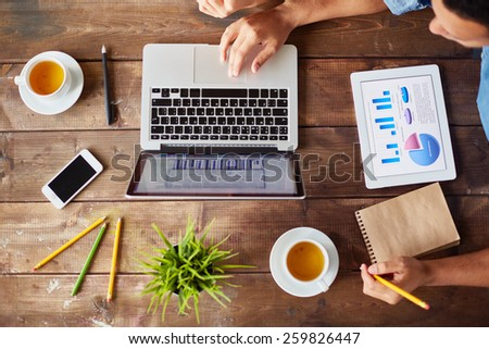 High angle view of table with laptop and man working with it - stock photo