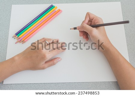 High angle view of the hands of a person sketching with colored pencils on a large blank white sheet of paper with a set of pencil crayons on top and one in his hand - stock photo