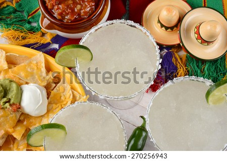 High angle view of three margarita cocktails surrounded by nachos, chips and salsa on a bright Mexican, table cloth. Horizontal format. Perfect for Cinco de Mayo projects. - stock photo