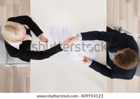 High Angle View Of Two Businesspeople Shaking Hand In Office - stock photo