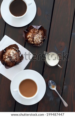 High angle view of two cups of coffee with two muffins - stock photo