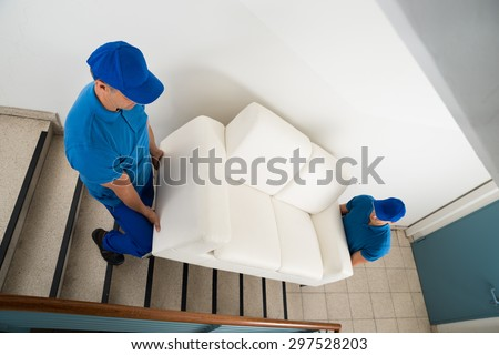 High Angle View Of Two Male Movers Carrying Sofa On Staircase Of House - stock photo