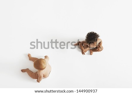 High angle view of two multiethnic babies looking in different directions isolated on white background - stock photo