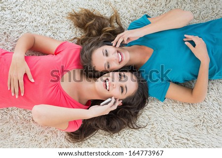 High angle view of two young female friends lying on rug and using cellphone in the living room at home - stock photo