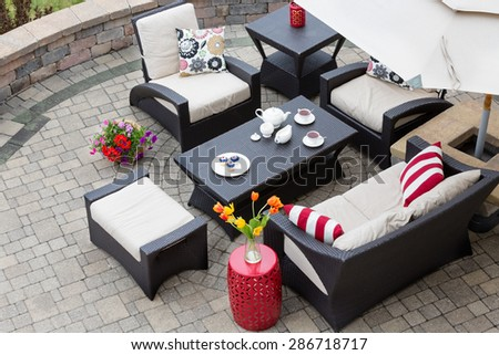High Angle View of Upscale Patio Set, Dark Wicker Luxury Furniture with Comfortable Cushions on Outdoor Stone Patio of Affluent Home - stock photo