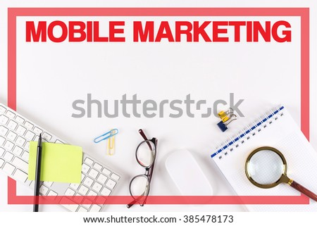 High Angle View of Various Office Supplies on Desk with a word MOBILE MARKETING - stock photo
