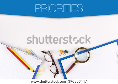 High angle view of various office supplies on desk with a word PRIORITIES - stock photo