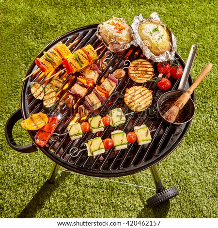 High Angle View of Various Vegetarian Kebabs and Vegetables Cooking on Grill with Basting Sauce in Sunny Yard on Summer Day - stock photo