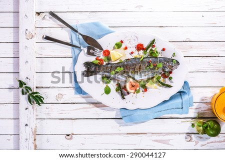 High Angle View of Whole Grilled Fish on White Platter with Garnish and Seasonings on Rustic White Wooden Table Surface with Blue Napkin and Cutlery - stock photo