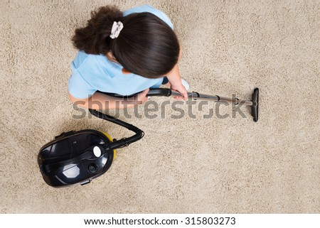 High Angle View Of Woman Cleaning Carpet With Vacuum Cleaner - stock photo