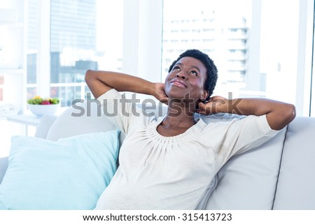 High angle view of woman looking up while relaxing on sofa at home - stock photo