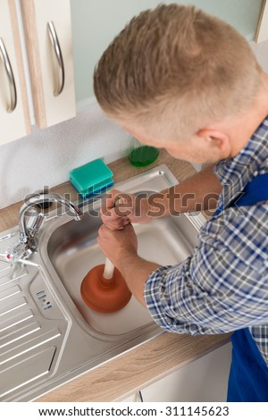 High Angle View Of Worker Pressing Plunger In Steel Kitchen Sink - stock photo